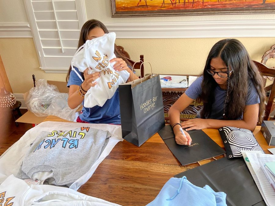 Isabelle and Sofia Rodrigues put together packages to ship out. Their business takes up a specific room in their house, and the girls work together to ship out their merchandise.