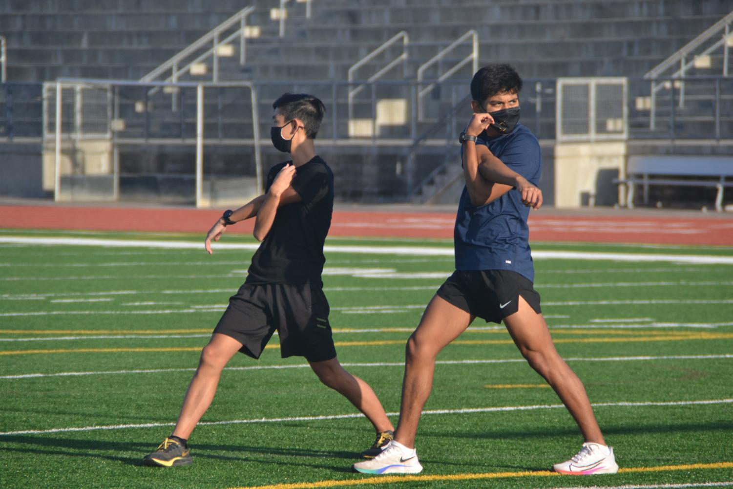 Jared Ho (11) and Nathaniel Lara (12) stretch after their warm up lap. Photo by Matthew Flores