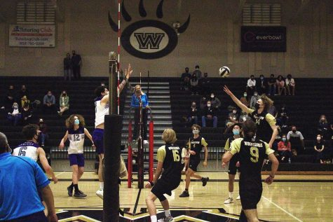 Outside hitter Caden Sajnog (11) attacks, scoring a point in the tight first game.