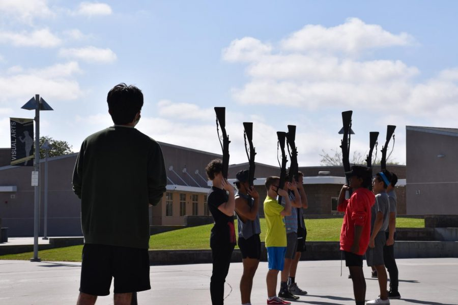 Jason Heflinger (12), left, leads the Armed Exhibition team as they practice the order toss sequence, a drill routine that involves throwing and catching rifles, May 6. Photo by Alice Chen.