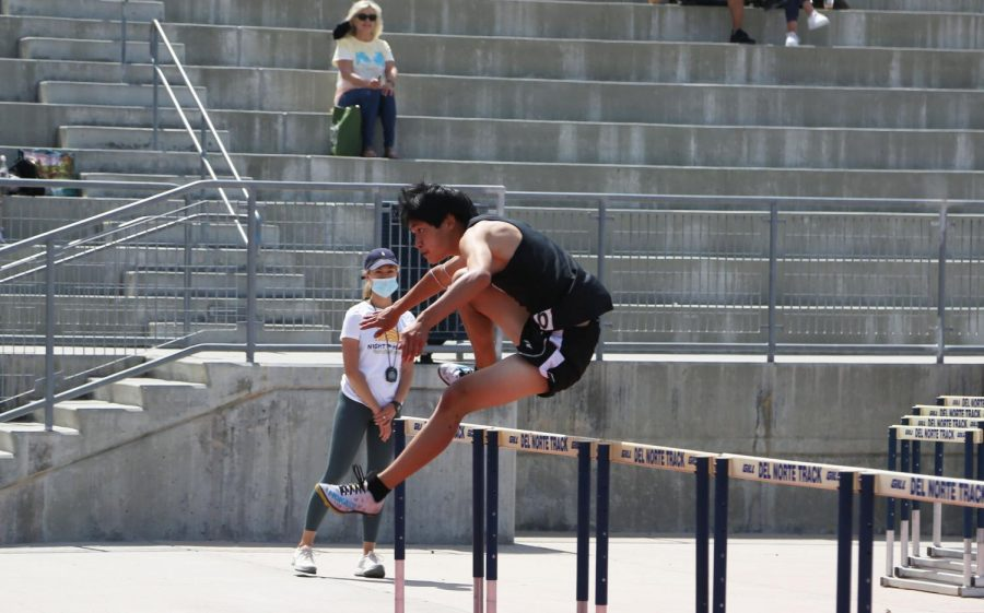 Justin Tong (11) lands a jump in the boys 110-meter hurdles. He finished first at the meet overall. Photo by Amy Wang.