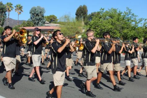The trombone section preps their horns to play a cadence of the Patriotic Parade Sequence. Drumline queues the band throughout the march to indicate when to play.