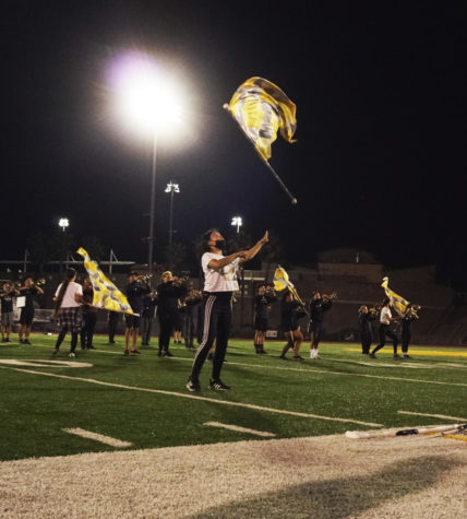 Tiffany Way (12) tosses her flag during a practice run of GOLDs show, Sept. 28. Photo by Byron Tran.