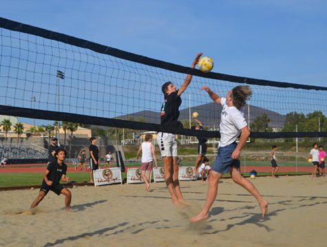 Luke Forster (12) blocks a spiked ball during beach volleyball practice while Marko Lipovic (12) gets ready to receive. Varsity members practice by playing king of the court with the junior varsity team to mentor the younger players. Photo by Jenna Ho-Sing-Loy.
